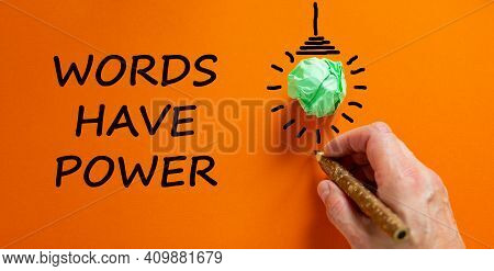 Words Have Power Symbol. Businessman Writing Text 'words Have Power', Isolated On Beautiful Orange B