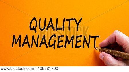 Quality Management Symbol. Businessman Writing Words 'quality Management', Isolated On Orange Backgr