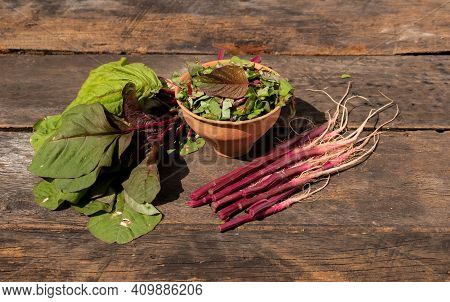 Red Spinach Or Amaranthus Dubius Leafy Vegetable Isolated On Wooden Background