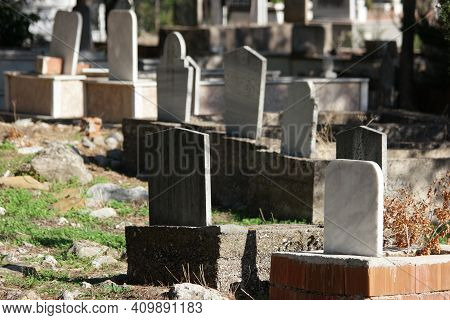 Tombstone And Graves In An Ancient Muslim Graveyard. Islamic Headstones And Memorials In Turkish Gra