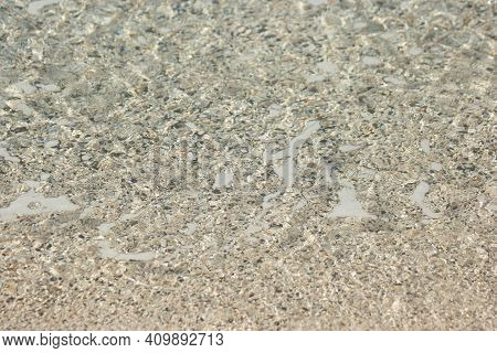 Sea Bottom With Small Stone Pebbles In Crystal Clear Water. Small Pebbles And Sand Seabed Background