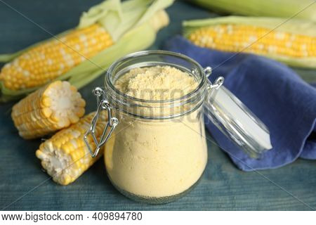 Corn Flour In Glass Jar And Fresh Cobs On Blue Wooden Table