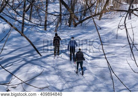 Montreal, Ca - 4 February 2021: People Skiing On A Snowy Trail In Montreal's Mount Royal Park (parc