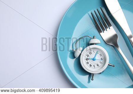 Alarm Clock, Plate And Cutlery On White Background, Top View. Diet Regime