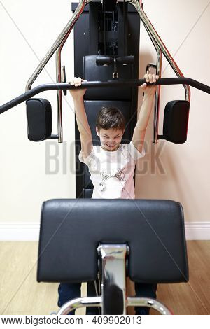 Boy Doing Exercises For Back Load On Simulator