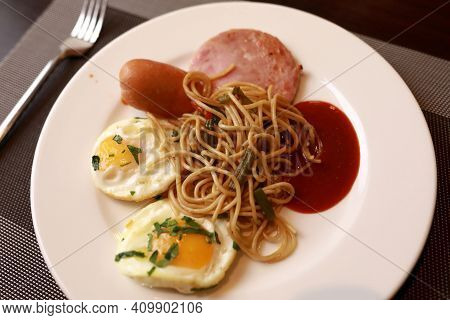 Fried Eggs With Spaghetti And Bacon On Plate