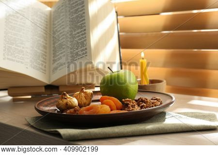 Dried Fruits, Apple, Bible And Candle On Window Sill Indoors. Great Lent Season