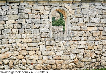 Stone Wall Of An Ancient Building With An Arched Window Over Which Other Ruins Are Visible