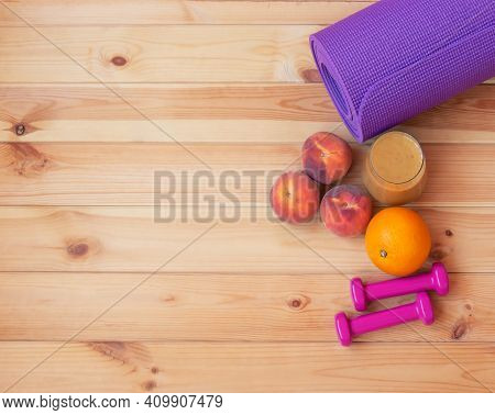 Pink Dumbbells, Yoga Mat, Fresh Fruits And Homemade Healthy Fruits Smoothie Made Of Oranges, Peaches