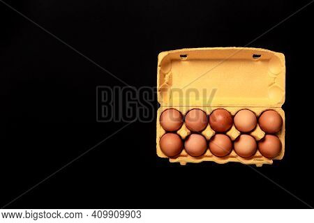 Natural Organic Chicken Eggs In Yellow Cardboard Package Isolated On Black Background, Top View, Wit