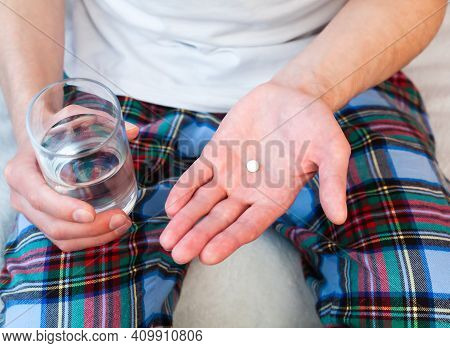 Young Man Holds One Pill And Glass Of Water In Hands. Taking Antibiotic, Antidepressant, Painkiller