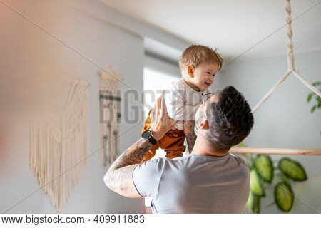 Father playing with his little son at home