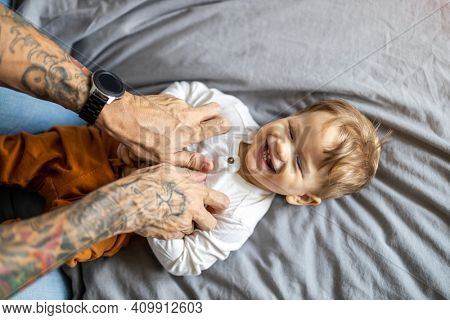 Father tickling his little son in bed