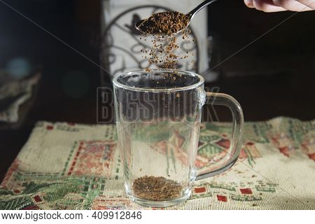 A Spoonful Of Instant Coffee. Coffee Is Poured Into A Cup.