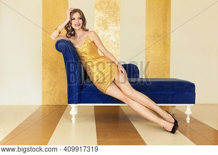Glamorous Celebrity Woman In Black Cocktail Dress And High Heels Shoes Sitting On Blue Velvet Sofa I