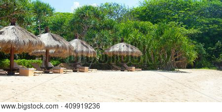 Empty Beautiful Idyllic Beach Panorama Background With Recliners, Chairs, Exotic Straw Tents, Palm T