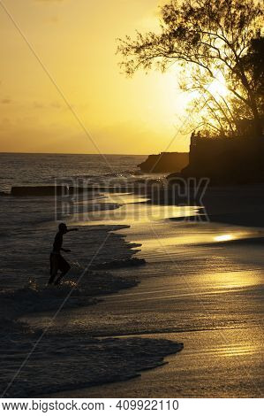 A Caribbean Sunset Over A Gentle Rolling Wave Beach In Silhouette. A Man Runs In From The Waves.