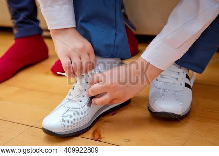 Child Put On A Pair Of Sneakers. Young Boy's Legs In Fashion White Sneakers. Children's Trendy Casua