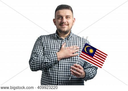 White Guy Holding A Flag Of Malaysia And Holds His Hand On His Heart Isolated On A White Background
