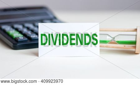 White Paper Card With Text Dividends, Calculator And Hourglass In The Background. Business And Econo