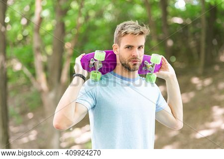 Hobby Concept. Man Smiling Face Posing With Penny Board Park Nature Background, Defocused. Guy Carri