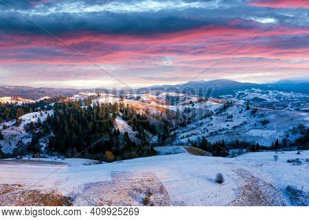 Amazing aerial view of mountains range and meadows of the countryside in spring time. Dramatic sky and snow-capped peaks glowing with bright sunset light. Lazeschina village, Ukraine, Carpathians