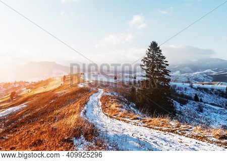 Amazing view of mountains range and meadows of the countryside in spring time. Clear sky and snowy road glowing with bright sunset light. Lazeschina village, Ukraine, Carpathians