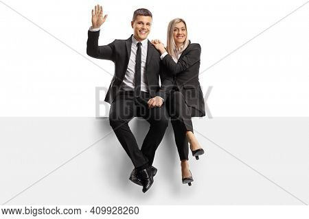 Professional man and woman in business clothes sitting on a blank panel and waving isolated on white background