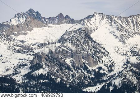 Rugged Mountain Peaks Covered With Snow And Glaciers Including An Alpine Conifer Forest At The Lower