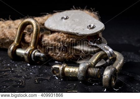Wet Shackles And Heavy Jute Rope Wrapped On Rollers In A Sailing Pulley. Accessories Used On Yachts