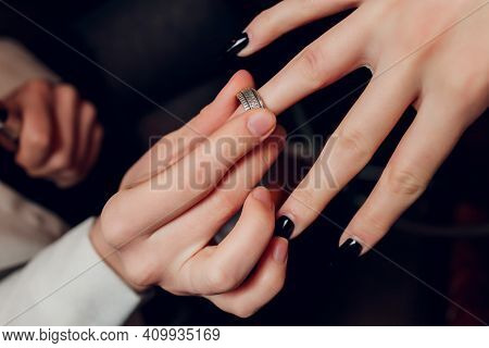 The Groom Puts A Ring On The Brides Hand. Newlyweds Exchange Rings, Groom Puts The Ring On The Bride
