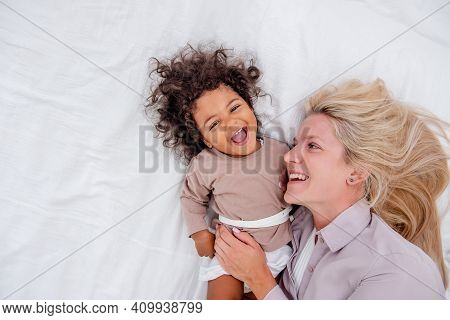 Young Caucasian Blond Mother Tickles Her Little African American Daughter. Lie On White Bed, Having