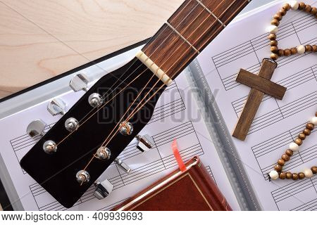 Conceptual Detail Of Christian Religious Music With Guitar Headstock On Sheet Music Book, Cross And