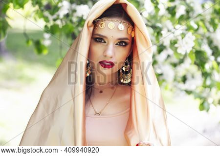 Young Pretty Indian Girl In Jewelry And Veil Posing Cheerful Happy Smiling In Green Park, Lifestyle