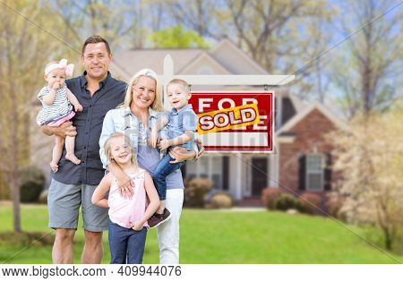 Happy Young Caucasian Family Outside In Front of Their New Home and Sold Real Estate Sign