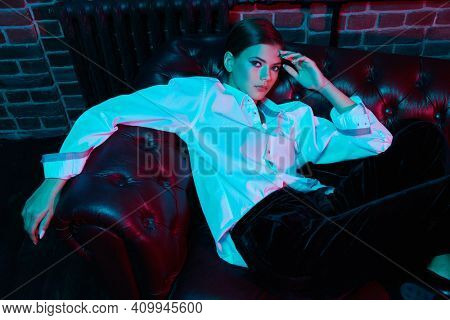Modern young woman posing in stylish black velvet suit and white shirt on a leather sofa. Luxurious lifestyle. Fashion, make-up and beauty trends.