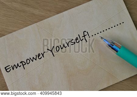 Pen And Wooden Board Written With Text Empower Yourself