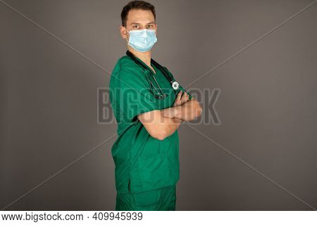 Portrait Of Young Male Doctor In Green Uniform With Stethoscope On Gray Background