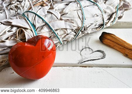 A Close Up Image Of White Sage And Holly Wood Smudge Sticks Next To A Heart Shaped Drawing.
