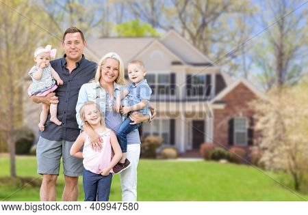 Happy Young Caucasian Family Outside  In Front of Their New Home.