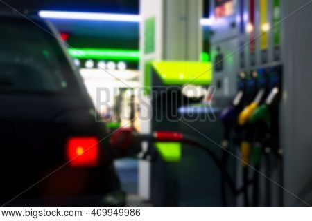 Gas Station At Night. The Car Is Fueled With Gasoline. Blurred Photo For Background.