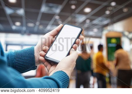 Mockup Of A Smartphone With A White Screen Close-up In A Person Hand, Against The Background Of A Re