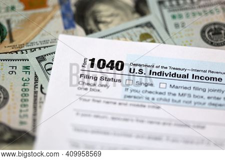 One Hundred Dollar Bills And Us 1040 Tax Form. Calculating Your Tax Refund