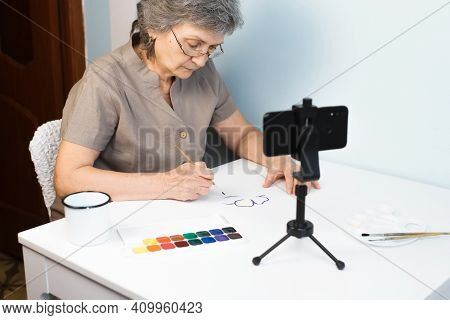 Elderly Woman With Glasses Painting Watercolors At Home. Pensioner Taking Painting Course Online. Ho