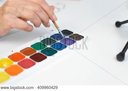 Woman's Hands Holding A Paintbrush And Painting With Watercolors, Close-up. Retirement Hobby Concept