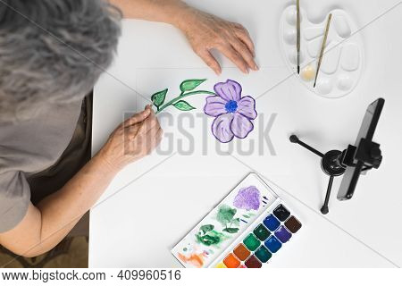 Female Hands Paint With Watercolors Indoors, Top View. Smartphone, Paints, Brushes On The Table. Onl
