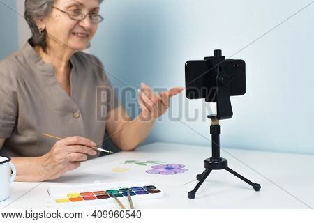 Smiling Senior Woman Taking Painting Course Online. Selective Focus On The Phone. Home Distance Lear