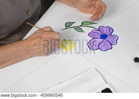 Female Hands Painting A Flower With Watercolors, Top View. Brush, Paints, Paper Lying On A White Tab