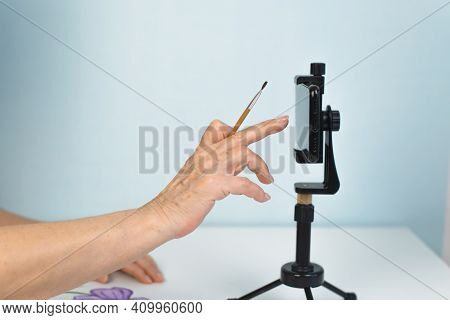 Female Elderly Hands Holding A Paintbrush And Using A Smartphone. Online Course On Drawing Concept.
