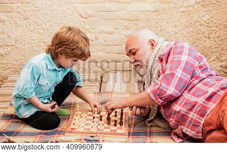 Grandfather And Grandson Play Chess. Generations. Checkmate. Senior Man Teaching His Grandson To Pla